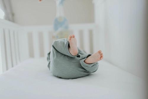baby lying insede a crib wearing gray pants
